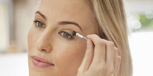 женщина красит глаз